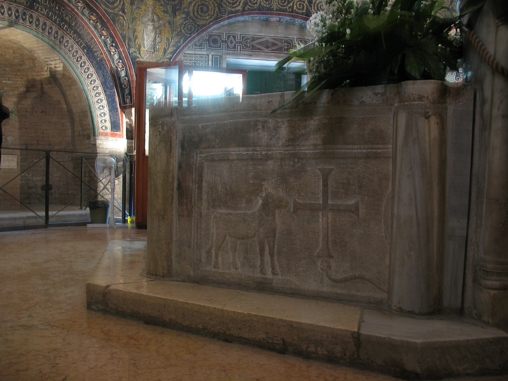 Λεπτομέρεια του εξωτερικού της κολυμβήθρας του ορθόδοξου βαπτιστηρίου της Ραβέννας (5ος αιώνας). Βλέπουμε ανάγλυφο έναν Αμνό με έναν Σταυρό.
