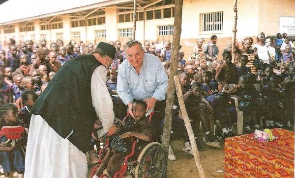 Εορταστική εκδήλωση στο Ορθόδοξο Σχολείο του Αγίου Ελευθερίου με τον Πανοσιολογιώτατο Αρχιμανδρίτης π. Θεμιστοκλή Αδαμόπουλο, προϊστάμενο του ιεραποστολικού κλιμακίου στην Σιέρα Λεόνε και και ο πρόεδρος της Αδελφότητος Ορθοδόξου Εξωτερικής Ιεραποστολής Θεσσαλονίκης με ανάπηρα παιδιά έξω από την πρόχειρη εκκλησία του Αγίου Ελευθερίου.