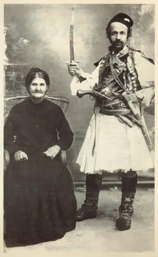 Ο Θεόφιλος φωτογραφίζεται  δίπλα στη μητέρα του  φορώντας φουστανέλα  και ζωσμένος άρματα,  με το σπαθί υψωμένο  ως ήρωας της Επανάστασης