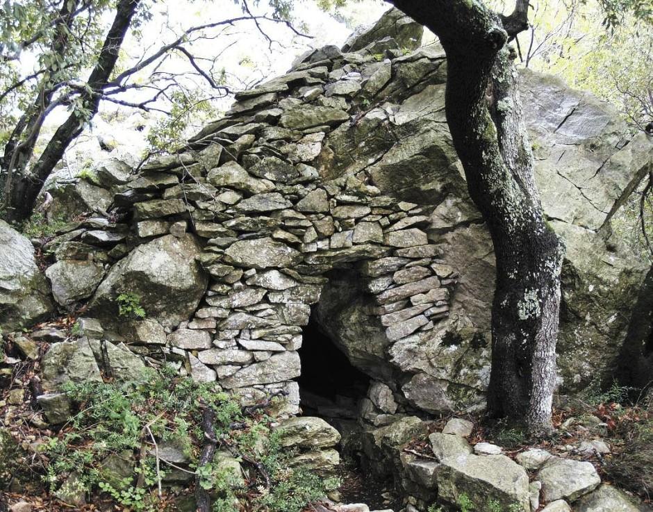 Ασκηταριό στα Καυσοκαλύβια κατασκευασμένο με τη συμπλήρωση ξηρολιθιάς στο φυσικό κοίλωμα, που προέκυψε από την τυχαία θέση ενός μεγάλου βράχου (τέλη 17ουαιώνα). Φωτ. Φαίδων Χατζηαντωνίου