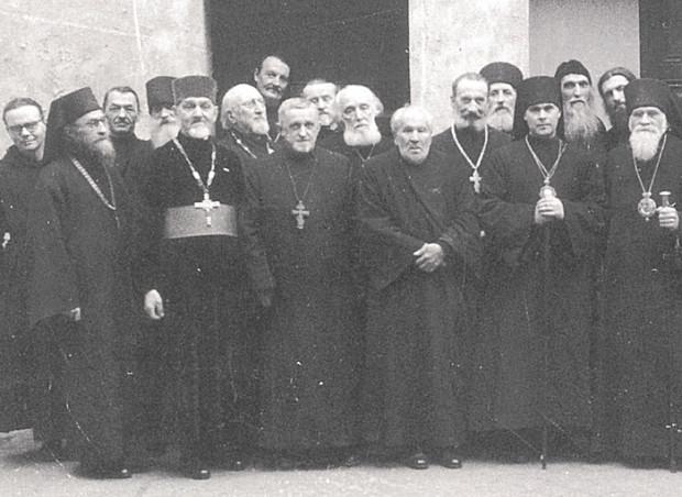 Photo prise le 30 Novembre 1957 devant l'entrée de l'église des Trois Saints Hiérarques, à l'occasion de la consécration de Monseigneur Antoine Bloom (quatrième à partir de la droite, imberbe). Le Père Sophrony et le Père Serge sont en deuxième et quatrième position à partir de la gauche.