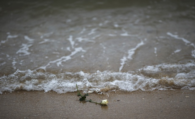 A rose is seen on the beach after being released by Thai children near a wave-shaped tsunami monument for victims of the 2004 tsunami in Ban Nam Khem, a southern fishing village destroyed by the wave December 26, 2014. Survivors of Asia's 2004 tsunami and relatives of its 226,000 victims gather along shorelines of the Indian Ocean on Friday for prayers and memorial services to mark the 10th anniversary of a disaster that still leaves an indelible mark on the region. In Thailand, where 5,395 people were killed, among them about 2,000 foreign tourists, commemoration ceremonies will be held in Ban Nam Khem. REUTERS/Athit Perawongmetha (THAILAND - Tags: DISASTER ANNIVERSARY ENVIRONMENT SOCIETY)