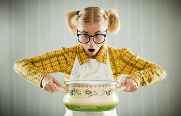 Blonde female geek in apron holding cooking pot looking confused.